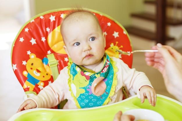 어머니는 숟가락으로 재미있는 아기를 먹입니다. 아이가 높은 의자에서 먹는다