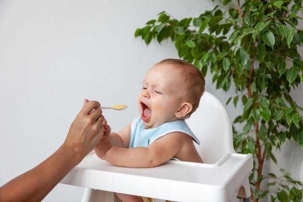 母はスプーンから青いよだれかけで小さな幸せな金髪の赤ちゃんを養う