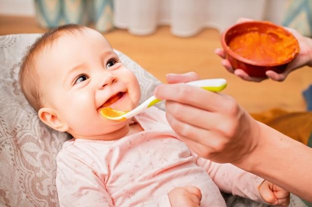 母親は、プラスチックスプーンから野菜のピューレで笑顔の赤ちゃんを養います