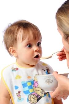 엄마는 놀란 아기에게 숟가락으로 먹이를 줍니다.