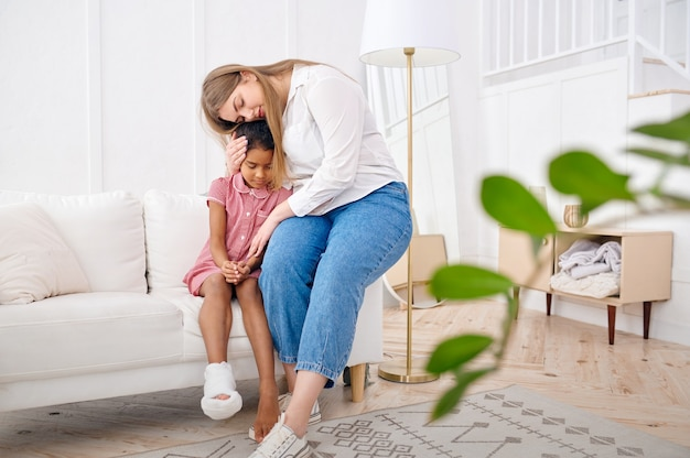 어머니는 거실 소파에 있는 어린 딸을 불쌍히 여기십니다. 엄마와 여자 아이는 함께 집에서 여가를 즐기고 좋은 관계, 부모의 보살핌, 사랑