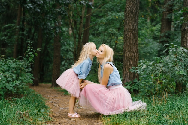 A mother and a five-year-old daughter in the same romantic clothes are walking in the park or in the woods.