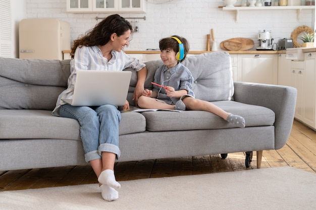 Mother freelancer enjoy helping little son with homework distance lessons as work remotely from home