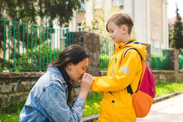 学校のお母さんが子供を学校の母親と生徒に連れて行く前に、母親は息子に優しくキスします