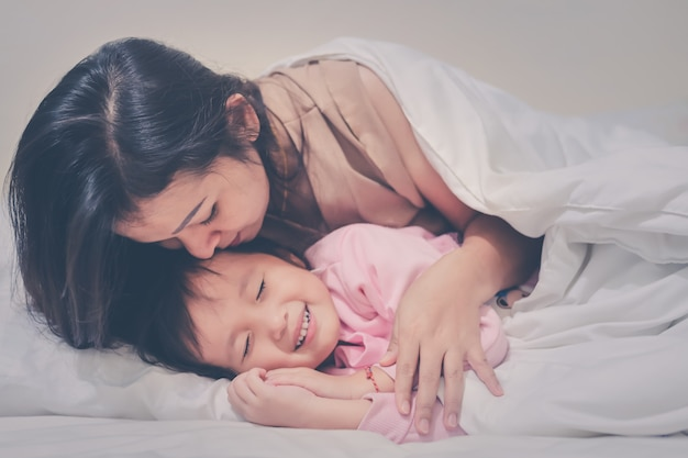 Mother gently kissing daughter wishing good night sweet dreams at night time soft focus happy family warm tone filter