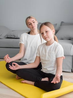 Mother and girl at home practicing yoga