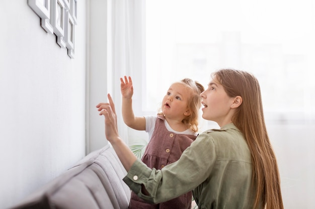 Mother and girl looking at frame