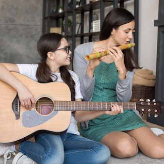 Mother and girl playing instrument