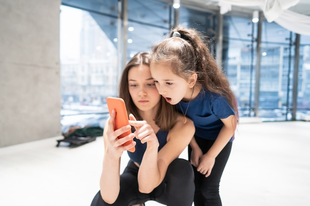 Mother and girl using phone in gym for watching video