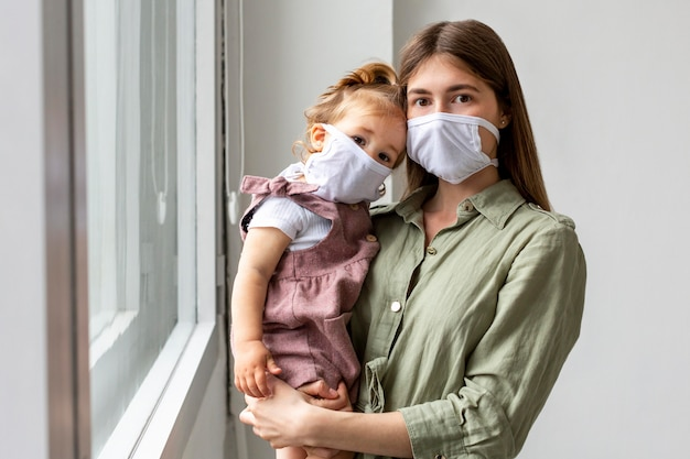 Mother and girl wearing medical masks
