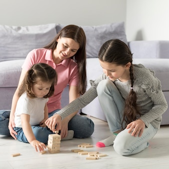 Mother and girls playing on floor