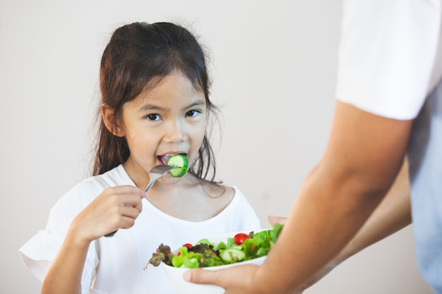 Mother give a bowl of salad to asian child girl to eat healthy vegetables for her meal
