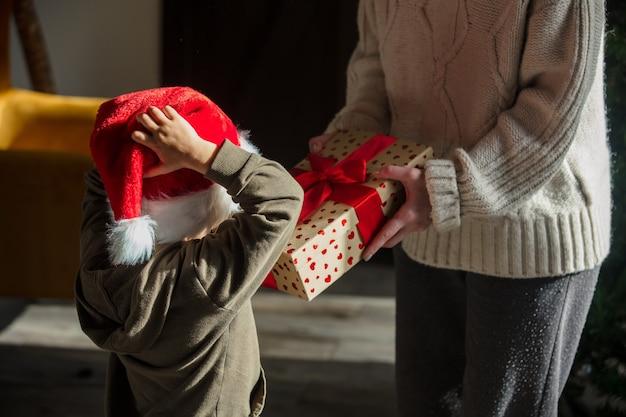 어머니는 크리스마스 모자를 쓴 아들에게 선물을 줍니다.