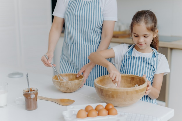 Mother gives culinary lesson to little child, stand next to each other, mix ingredient in big wooden bowls