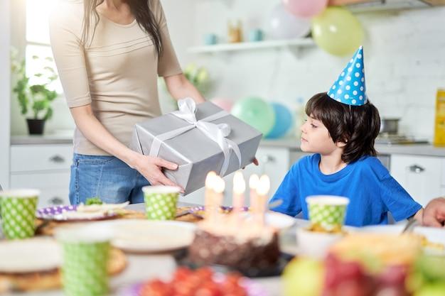 어머니는 집에서 아이의 생일을 축하하면서 저녁 식사를 하는 동안 사랑스러운 어린 소년에게 선물 상자를 줍니다. 선택적 초점입니다. 가족, 축하 개념