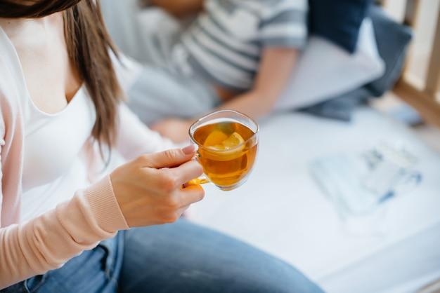 母親は病気やウイルスの最中にレモンと一緒に熱いお茶を赤ちゃんに与えます。薬とケア。
