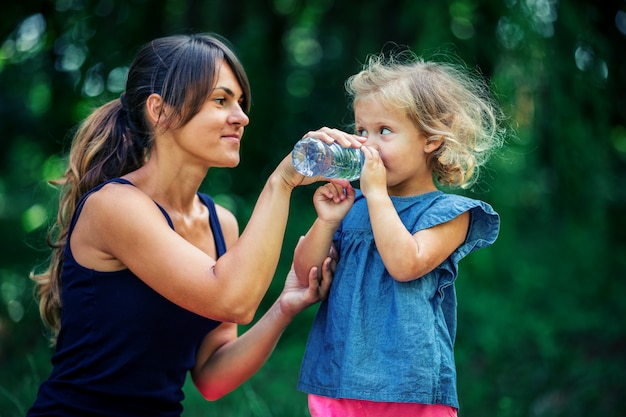 Mother gives a little girl to drink water