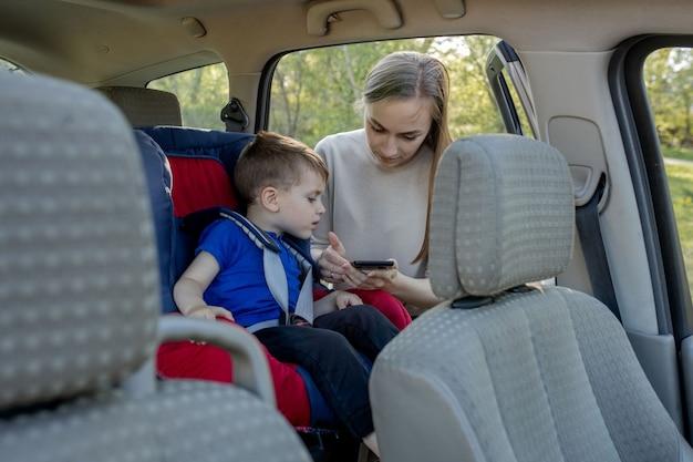 母はチャイルドシートに座っている男の子にスマートフォンを与えます