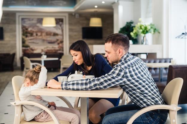 Мать дает утешение плачущей дочери в ресторане