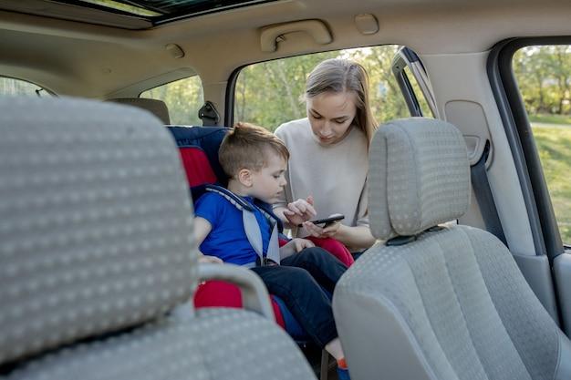 母は車の座席に座っている小さな男の子を電話に渡します。子供の輸送の安全性