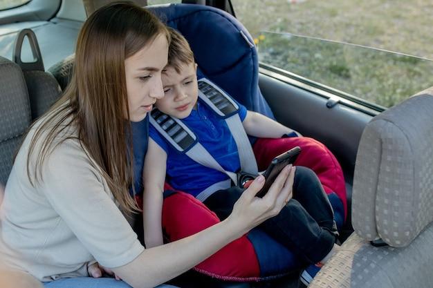 母は車の座席に座っている小さな男の子を電話に渡します。子供の輸送の安全性。