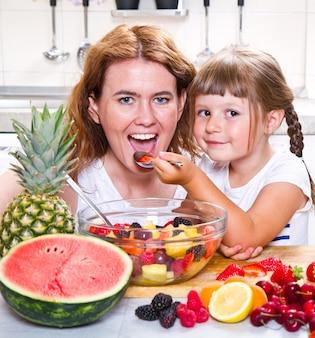 어머니는 어린 소녀에게 부엌에서 과일 샐러드를 제공합니다.
