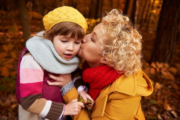 頬にキスの女の子を与える母