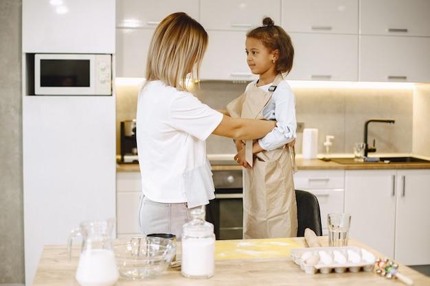 娘にエプロンをあげる母。小さな民族の子供と一緒に料理をする幸せなお母さんの世話をする