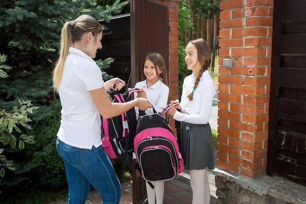朝学校に通う娘たちにバックパックを渡す母親
