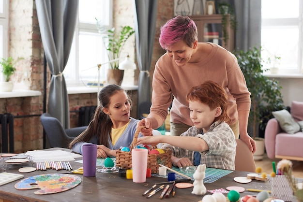 Мать дает корзину с яйцами и дети, украшающие их на праздник
