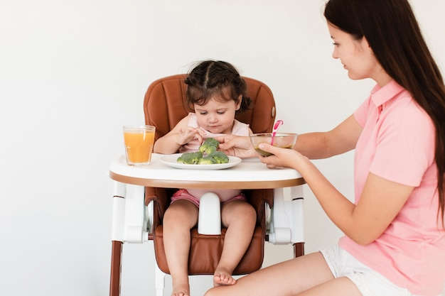 Mother giving broccoli to her daughter