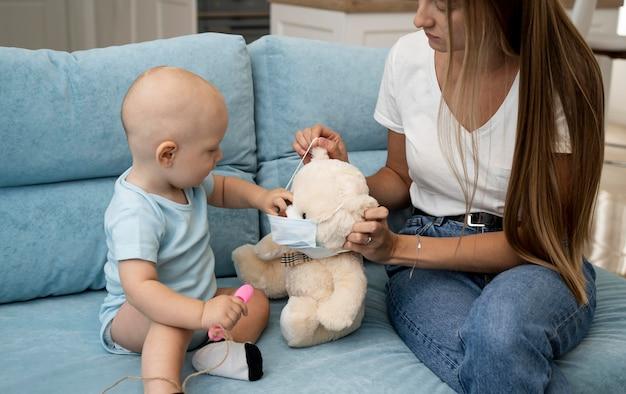 Мать дает ребенку плюшевого мишку с медицинской маской