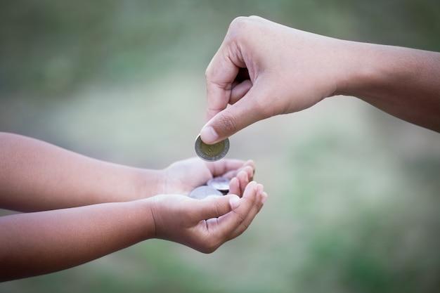 Мать, дающая монеты ребенку, как концепция экономии денег в старинном цветовом тоне