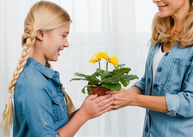 Mother giving to daughter flower pot