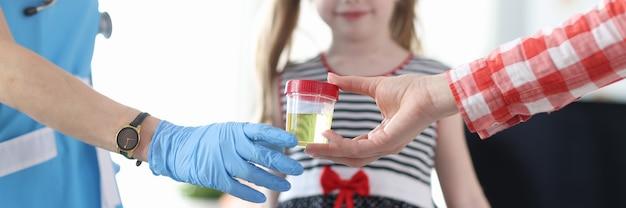 小さな女の子のクローズアップの前で尿分析の医者の瓶を与える母