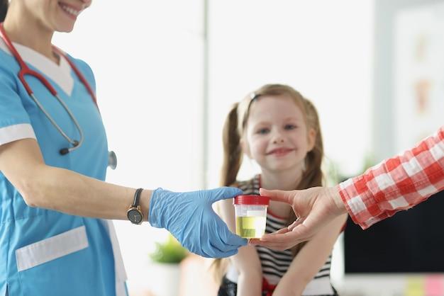 병원 근접 촬영에서 아이 앞에서 소변의 의사 항아리를주는 어머니