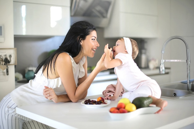 Mother giving food to her baby in the kitchen
