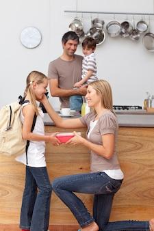 女の子、学校の昼食をキッチンで与える母親