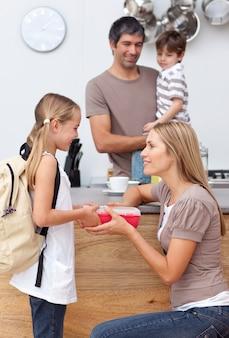 彼女の娘に学校の昼食を与える母