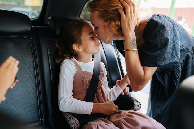 Mother giving her eight year old daughter a kiss. she's sitting on a back seat in a car. from inside a salon.