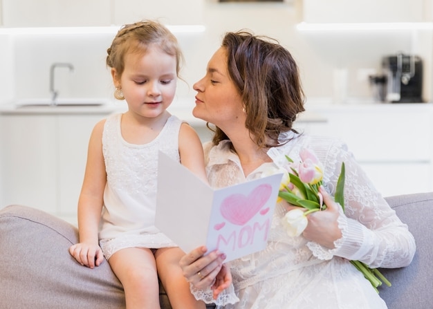 Mother giving kiss to her cute little daughter holding greeting card and flower bouquet