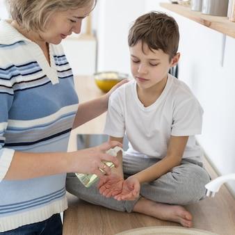 子供に液体石鹸を与える母