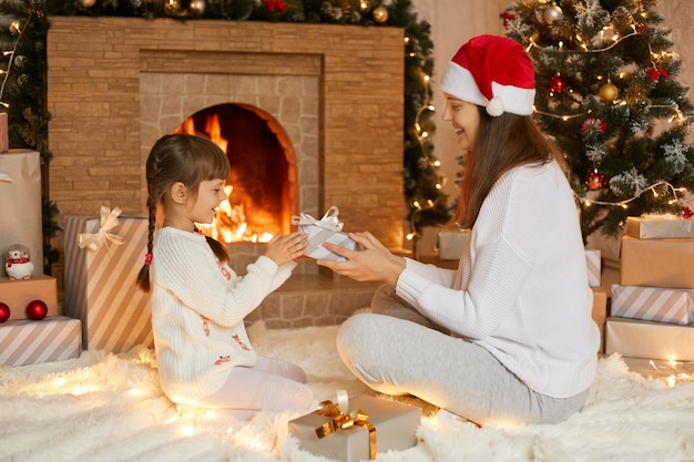 小さな娘にプレゼントボックスを贈るお母さん、笑顔の女の子がプレゼントに満足のいく表情で見え、白いシャツを着た女性が暖炉とモミの木の近くに座っています。