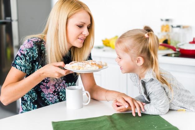 娘にお菓子を与える母親