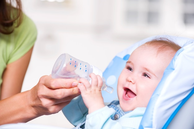 赤ちゃんに水を与える母