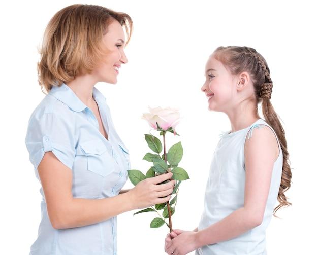 白いバラを彼女の小さな娘に与える母親-孤立した