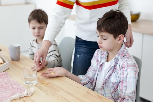 Мать дает детям витамины, чтобы защитить их от вируса