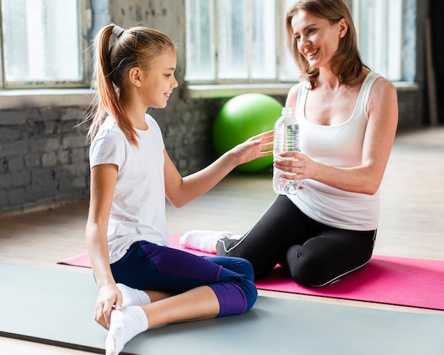 Mother giving water bottle to daughter in gym