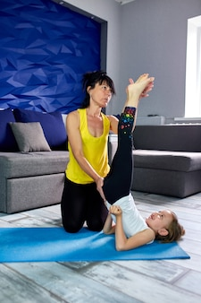 Mother or grandmother and her daughter doing gymnastic together at home.