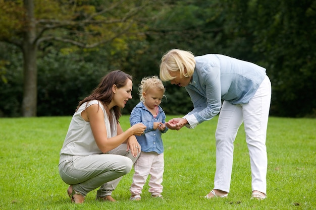 Mother and grandmother showing little girl flower